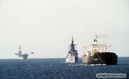 A starboard bow view of ships from a tanker convoy underway in the Persian Gulf during Operation Earnest Will. Included in the convoy are the reflagged tanker GAS KING, the U.S. Navy guided missile cruiser USS WILLIAM H. STANDLEY (CG-32) and the amphibious assault ship USS GUADALCANAL (LPH-7).