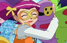 Jessie, a redhead in pigtails and large orange glasses, hugs a giant purple moth with green wings and yellow eyes: the pokemon Dustox.