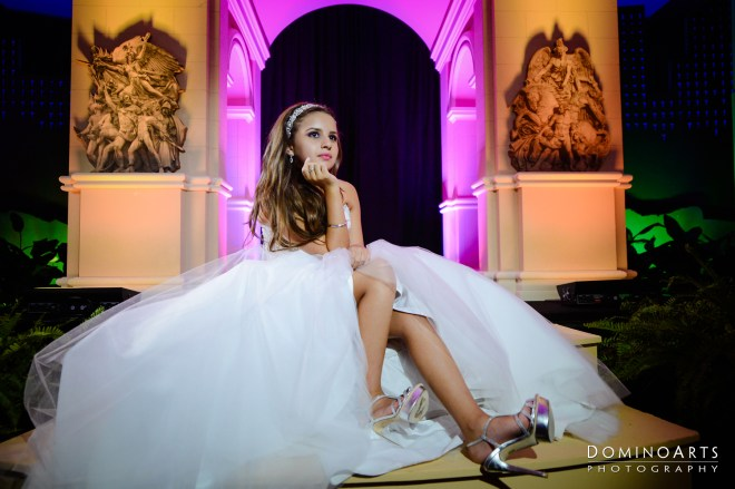 A ttenage girl in an expansive formal gown, sitting on steps. In the background, an ornate arch is lit in soft magenta and green, with darkness behind. She wears high-heeled shoes and a formal hairstyle.