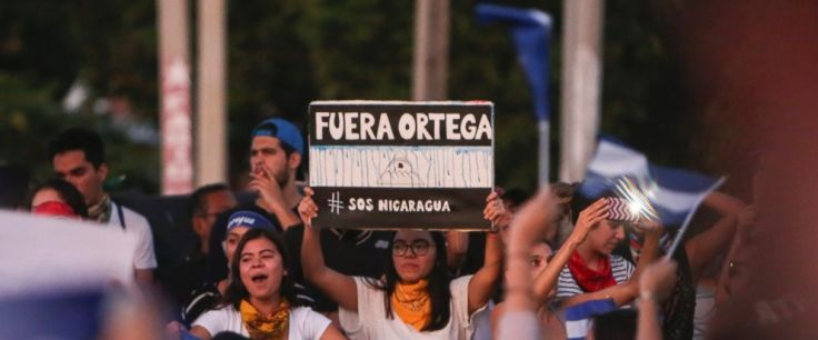 "A woman holds a sign that reads in Spanish ""Ortega Out,"" during a protest against the government of President Daniel Ortega, in Managua, Nicaragua, Sunday, April 11, 2018. President Ortega has withdrawn changes to the social security system that touc"