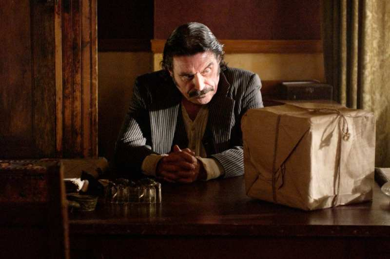Al looks glumly at a box in brown paper on his desk