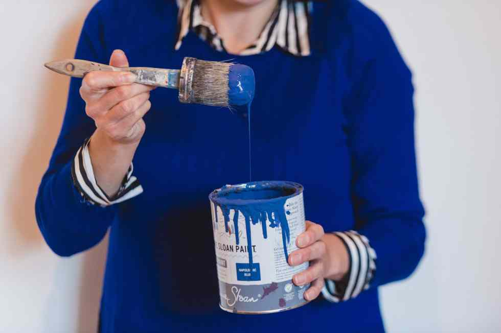 Carrie Webb dripping blue paint into a paint tin.