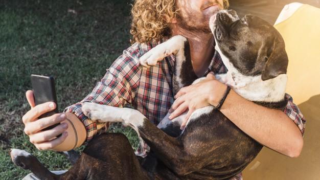 Homem segurando o cachorro para tirar uma foto