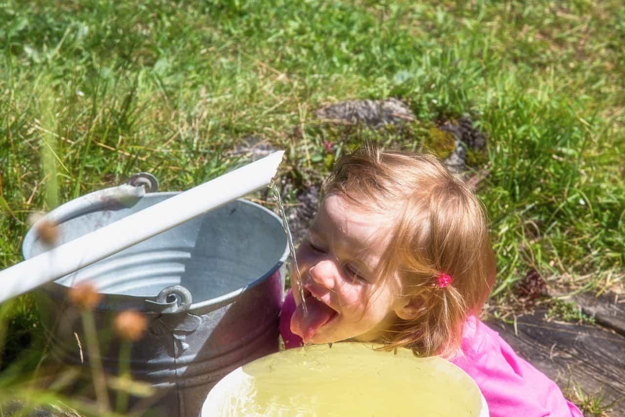 Ein Mädchen trinkt frisches Quellwasser