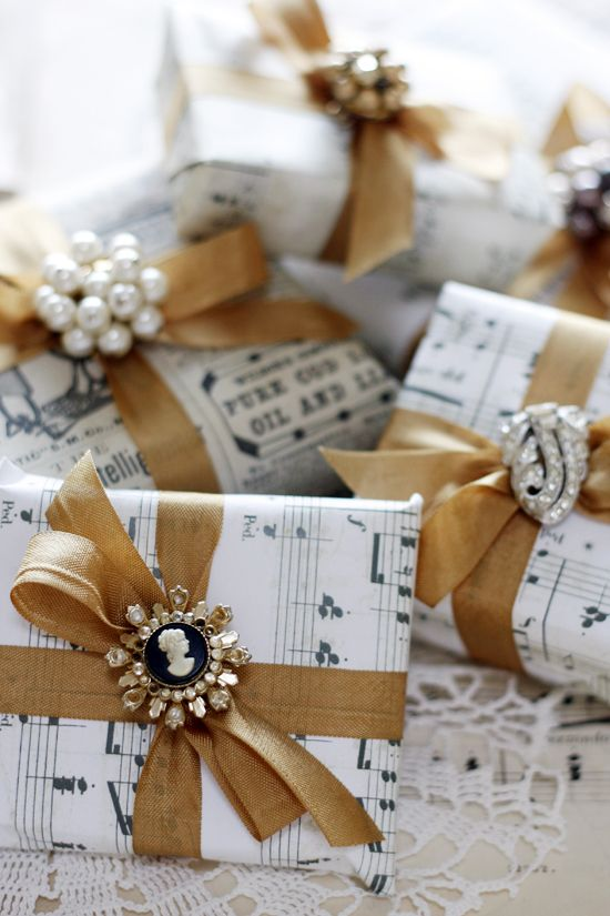 Create an elegant centerpiece with little gift boxes wrapped in vintage sheet music and clippings. Finish