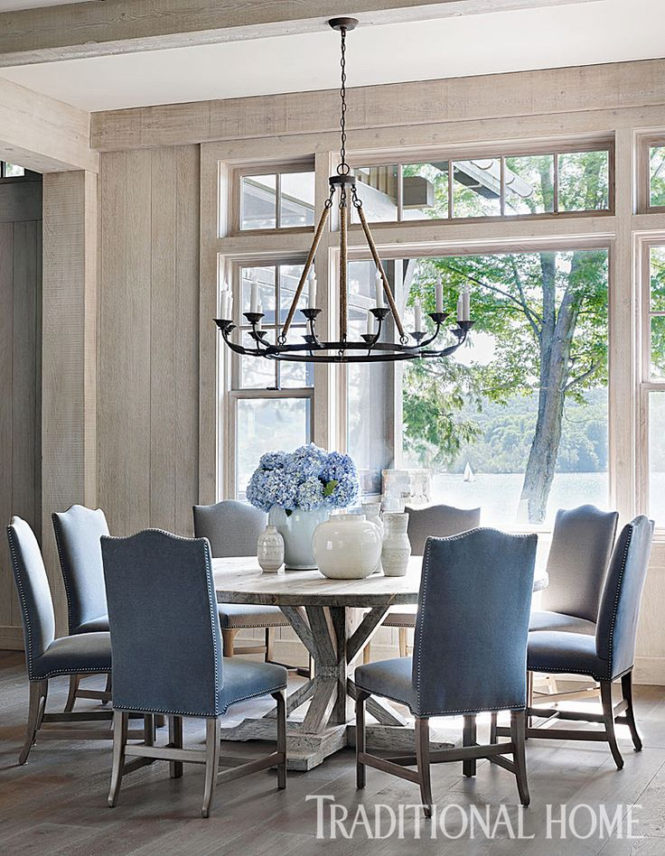 """A """"Lola"""" chandelier from Bungalow Classic hangs above the round elm dining table. Floors throughou"""