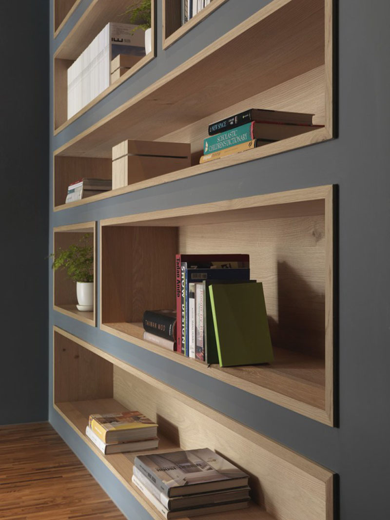To make the built-in bookshelves on this deep grey wall stand out, the shelves were lined with wood to add a natural touch and