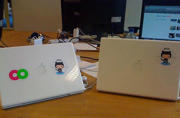 GitHub octocat logo stickers on MacBook