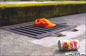 A crumpled orange cap sits abandoned on a metal storm grate near a discarded can of Slim Fast.