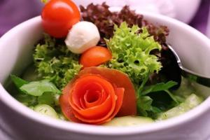 A delicious salad, featuring tomatoes curled into a rosette, in a white bowl.