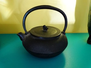 A vintage Japanese teapot with a dark patina sits on a teal surface against a yellow-green background.