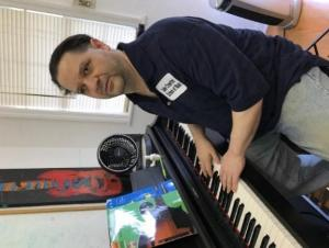 John Crawford , a dark-haired man in a navy blue collared shirt, sitting at a piano.