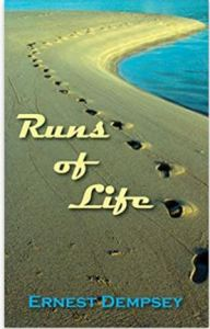 "The cover of ""Runs of Life"" shows a single set of footprints in the sand beside a blue body of water."