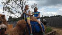 Courtney and Natalie riding a camel