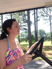 Natalie happily driving the golf cart