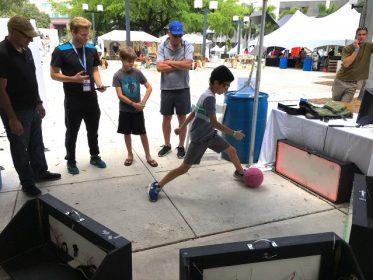 Kid kicking ball at skill court