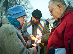 Rev. Al Schon of Peace United Church of Christ lights the candles of two vigil-goers at a prayer vigil on Monday, March 25 at the First Congregational Church of Webster Groves. People gathered that evening hoping the U.S. Supreme Court will allow more Americans to be in same-sex marriages. Schon has been in a relationship with his partner for 24 years. They married in 2008 when California passed legislation allowing same-sex marriages. Schon said he hopes same-sex couples will have the same rights as heterosexual couples. PHOTO BY BRITTANY RUESS