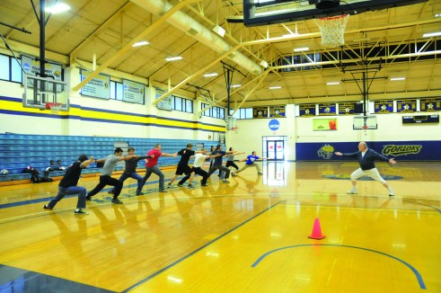 PHOTO BY MEGAN WASHAUSEN / The Journal Adjunct professor Michael Long leads lunge exercises in his Fencing II class to teach his students proper form and technique. The class meets on Tuesdays and Thursdays in Grant Gymnasium from 11:30 a.m. to 12:50 p.m.