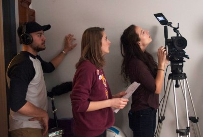 "Jamil Ziadi (left), Director/Co-Writer Jenna McDonald (center) and Cinematographer Katie Ploessser (right)  prepare a scene for ""June,"" which McDonald wrote with her sister. / photo by Hayden Andrews"