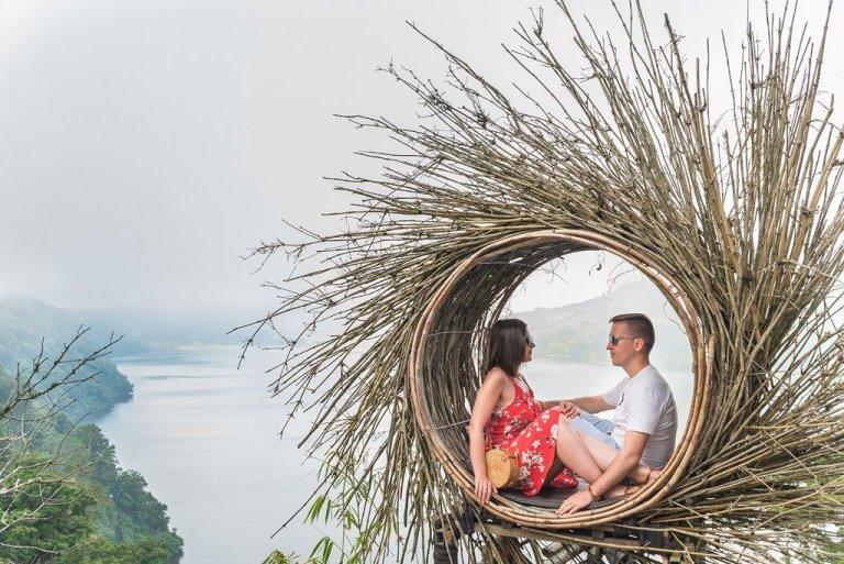 Pareja de jovenes viajeros del We Collect Postcards en el nido del lago Buyan en la isla de Bali, Indonesia