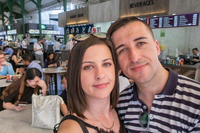 Pareja de jóvenes viajeros de We Collect Postcards en el Telok Ayer Hawker Centre - Singapur