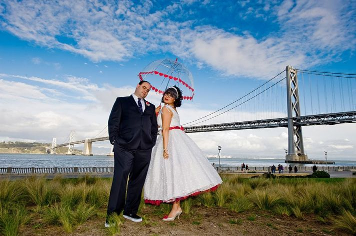 https://i2.wp.com/wedding-pictures-05.onewed.com/14509/retro-bride-white-wedding-dress-red-peticoat-poses-with-groom-near-lake-heart-umbrella-valentines-themed-wedding__full.jpg