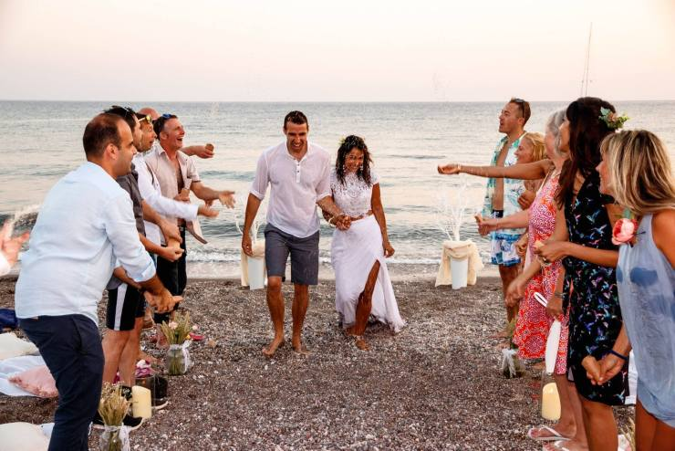 A just married couple at their beach wedding walk from the sea through 2 lines of their friends who are throwing confetti. A destination wedding in Tilos, Greece with a wedding celebrant.