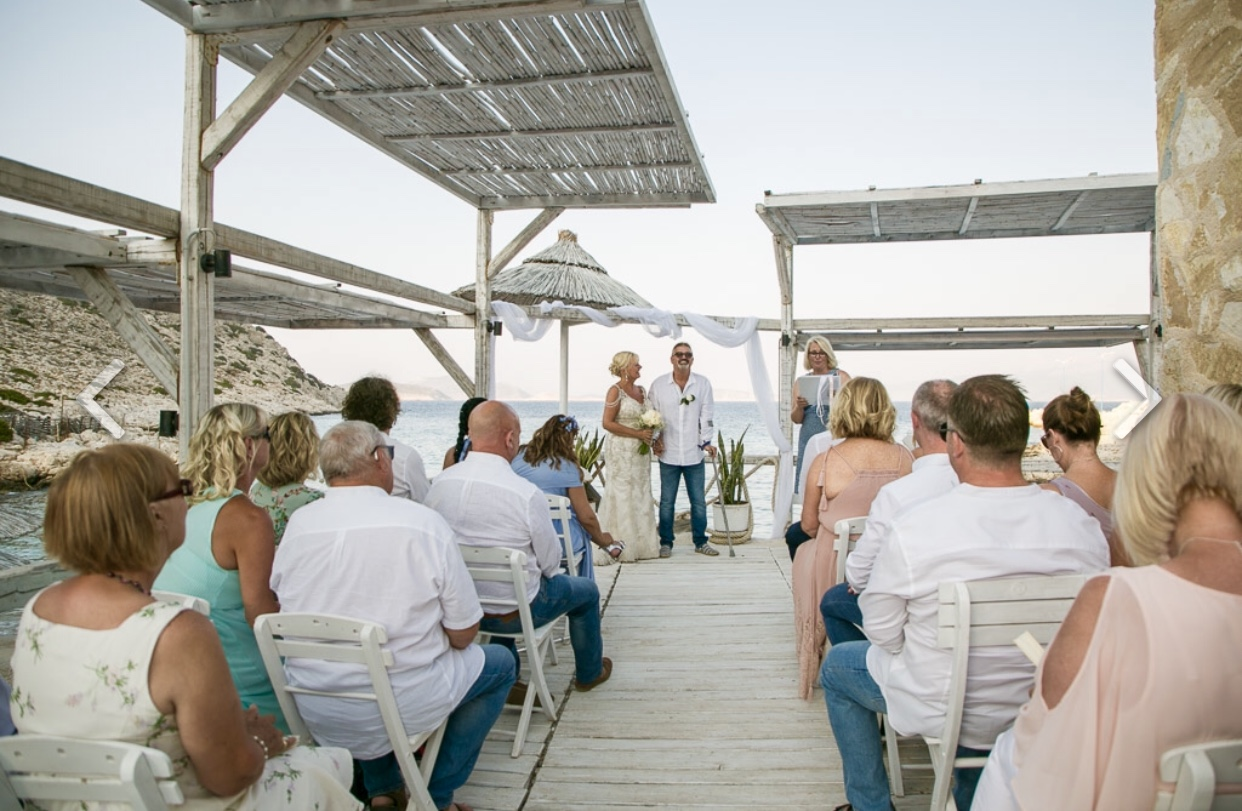 A Greek beach wedding ceremony in Halki, Greece. The photo shows the guests seated and the couple in the bckground with the Celebrant and a view of the sea.