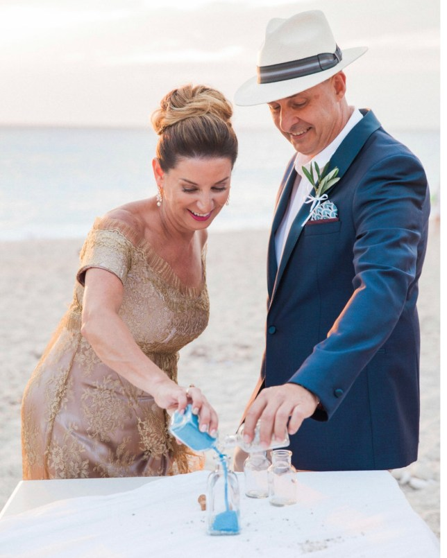 A mature couple complete a sand blending ceremony in a Greek beach wedding ceremony, led by wedding celebrant ECK - a wedding celebrant in Greece