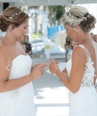 Two brides in a same sex wedding ceremony exchange wedding rings. The ceremony was created by ECK-A wedding Celebrant in Greece