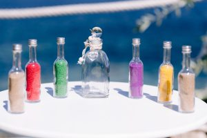 Different coloured sand in bottles are around an empty bottle which will be used for a sand blending unity ceremony. The blue sea in the background is a beautiful setting for this greek island wedding performed by ECK - A wedding Celebrant in Greece