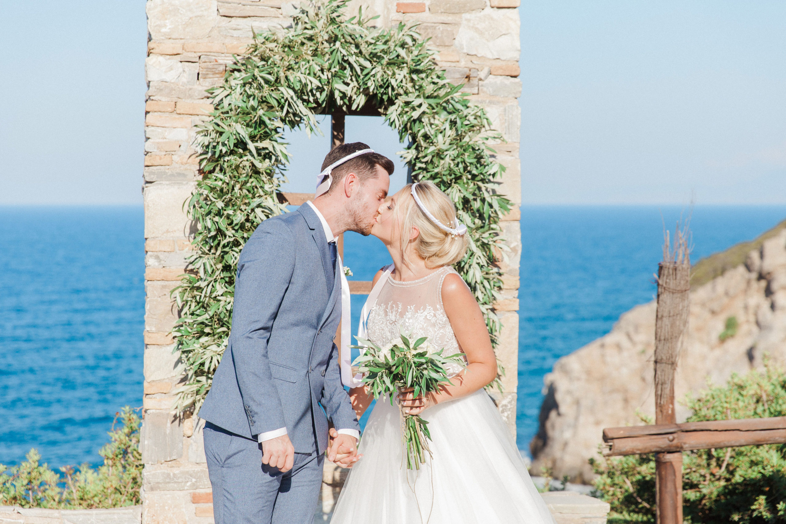 The couples first kiss at the end of their celebrant led wedding ceremony at Villa Delenia in Evia Greece. The couple are wearing Greek wedding crowns.
