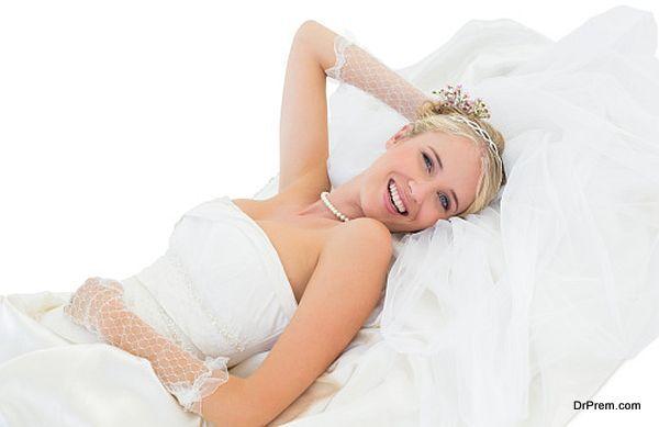 Happy sensuous bride lying against white background