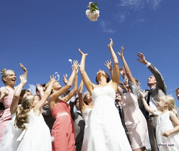 Bride Throwing Bouquet For Guests To Catch