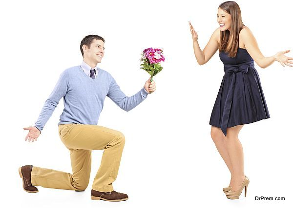 Male kneeling with a bunch of flowers and excited female