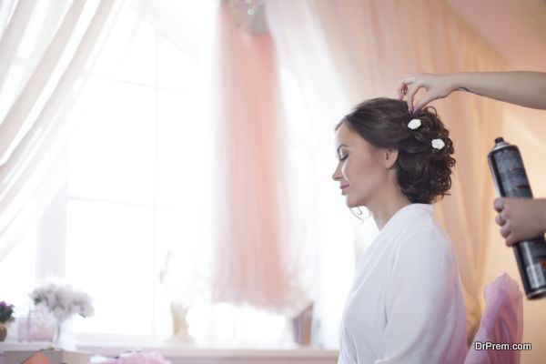 Stylist pinning up a bride's hairstyle