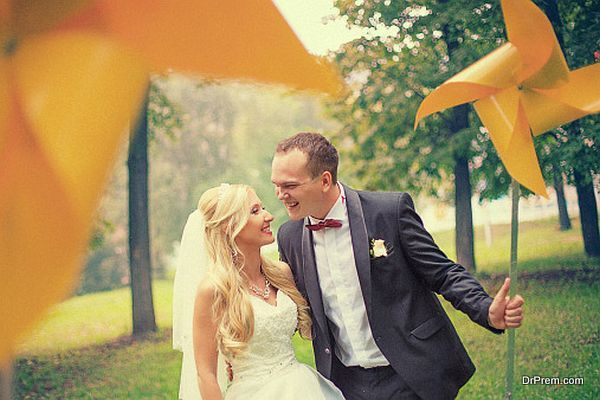 Newlyweds are in a park with toy wind turbine