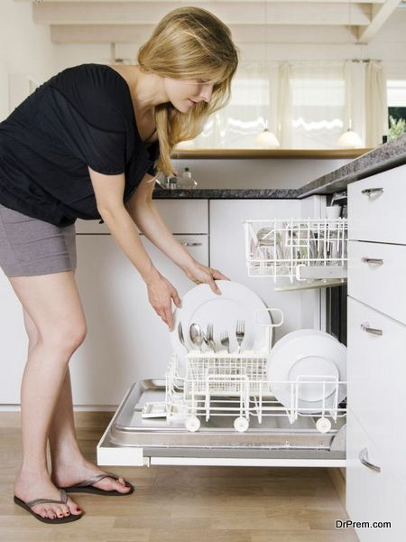 Photo of a blond female leaning over and unloading her dishwasher.