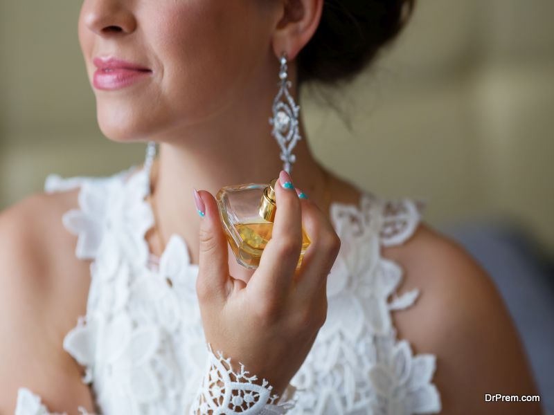 Bride spraying perfume on her neck
