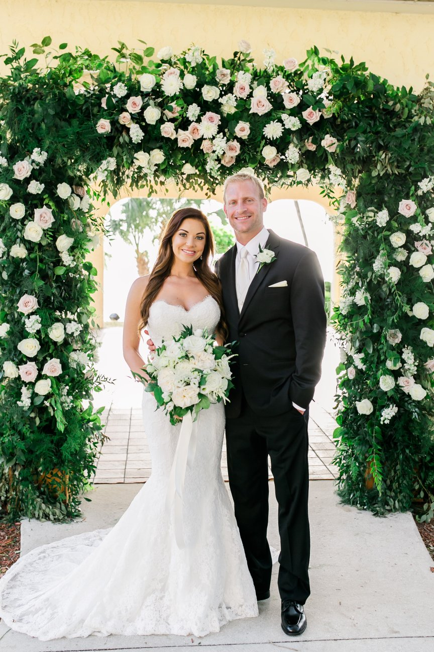 Bride and Groom Under Wedding Arch with Flowers and lots of Greenery