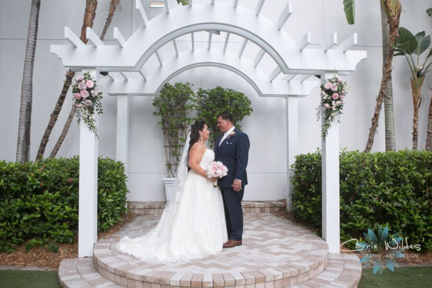 Bride and Groom Under Wedding Gazebo with Pink Floral Sprays