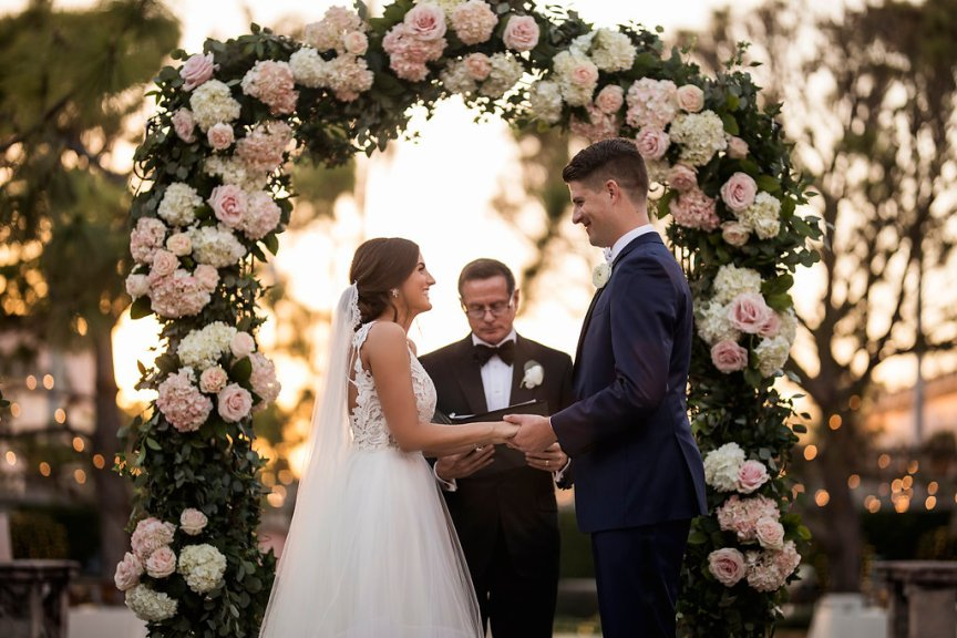 Bride and Groom Under Blush and Soft Peach Flower Arch with Lots of Greenery