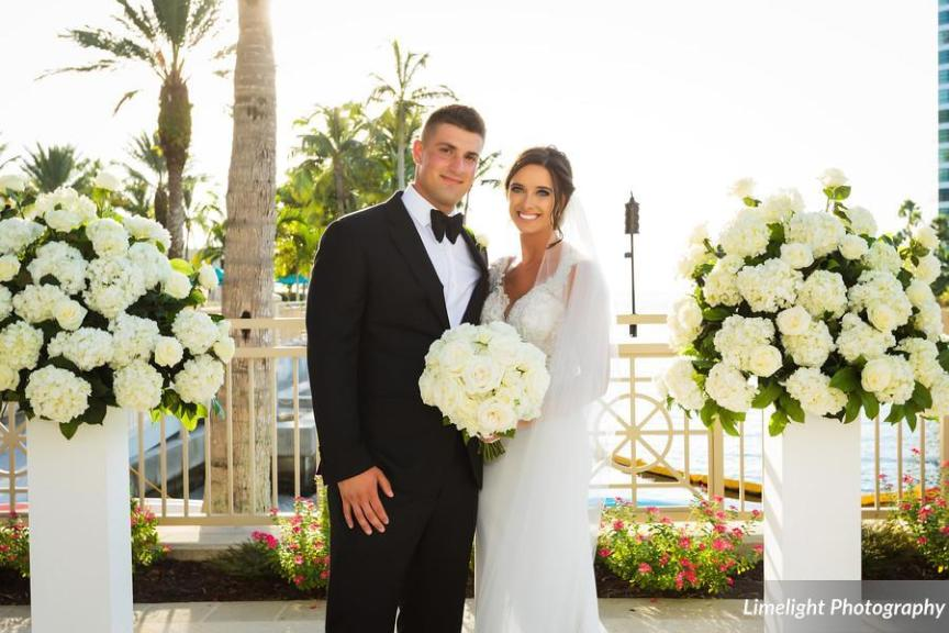 Bride and Groom surrounded by large all-white flower arrangements