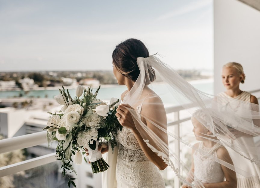 Bride with all-white bouquet on Balcony overlooking the water