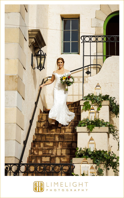 Bride Going Down Stairs decorated with Greenery and Gold Lanterns