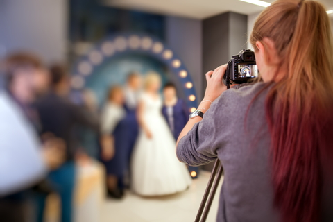 photographer taking pictures of bride and groom - posed photos