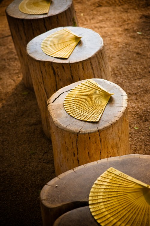 yellow fans at rustic wedding ceremony
