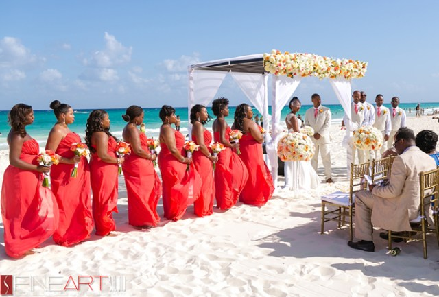 A bride and groom having their wedding ceremony on the beach in Playacar Palace, Mexico
