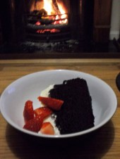 With strawberries in front of a cosy fire