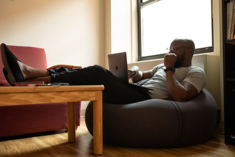 man sitting with a laptop to become an African freelance writer